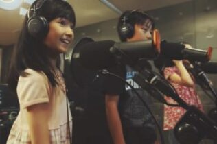 Two kids singing into microphones