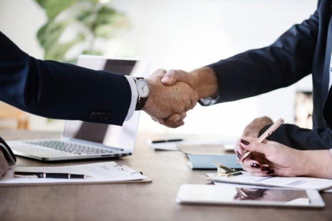 Partner Handshake At Desk
