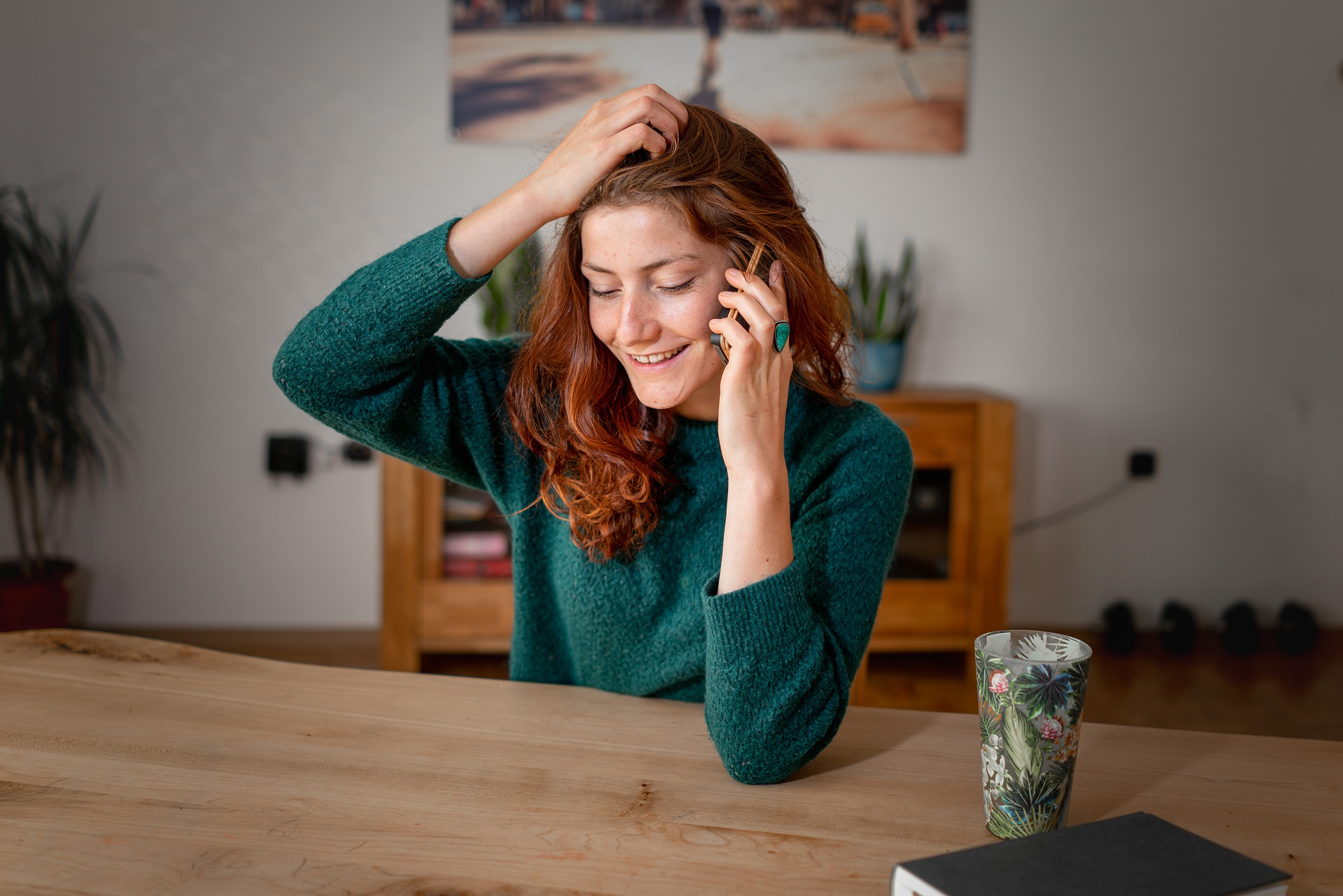 Woman in green dress talking on the phone at a table.