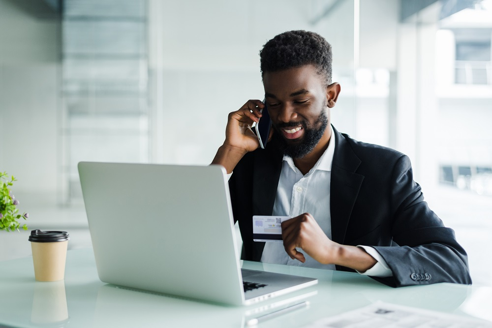 Man talking on phone with credit card in hand in front of laptop