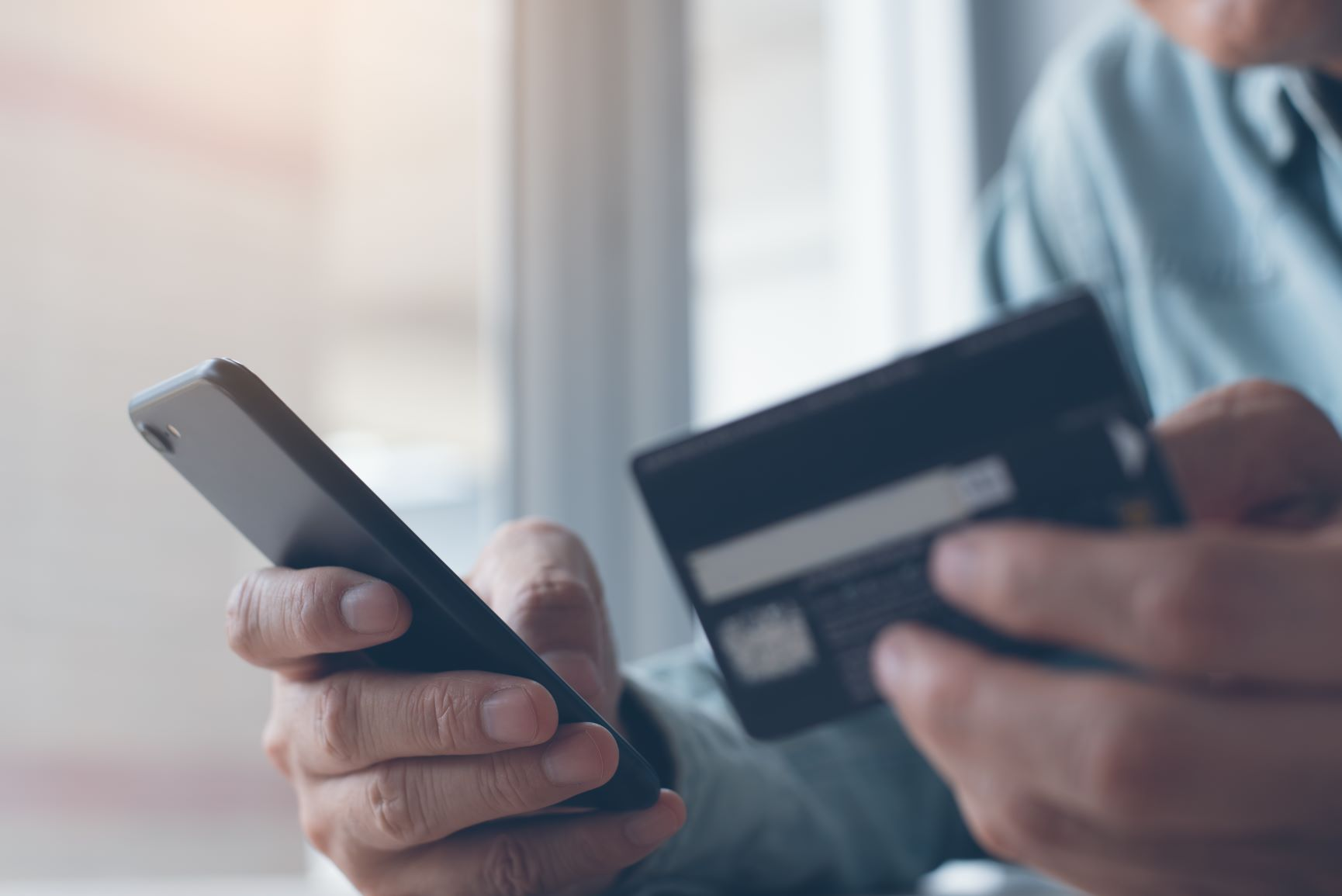 closeup man holding smart phone typing in credit card numbers